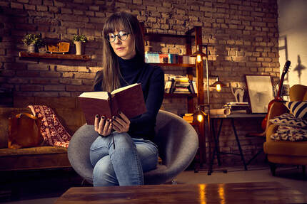 Woman sitting on a chair reading a book, feeling concerned about PTSD and needing EMDR therapy for sexual trauma therapy in Minneapolis, MN and beyond with online therapy in Minnesota